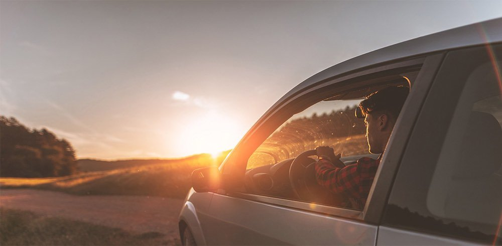 Man driving his vehicle in a rural setting with the sun shining down on him