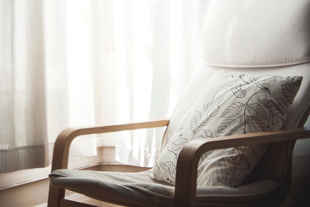 Close up of a chair with a pillow on it infront of a bright window